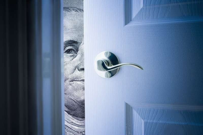 door opening with Franklin $100 staring through the crack