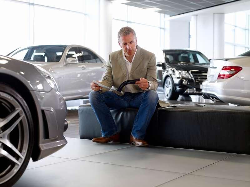 man in car dealership showroom
