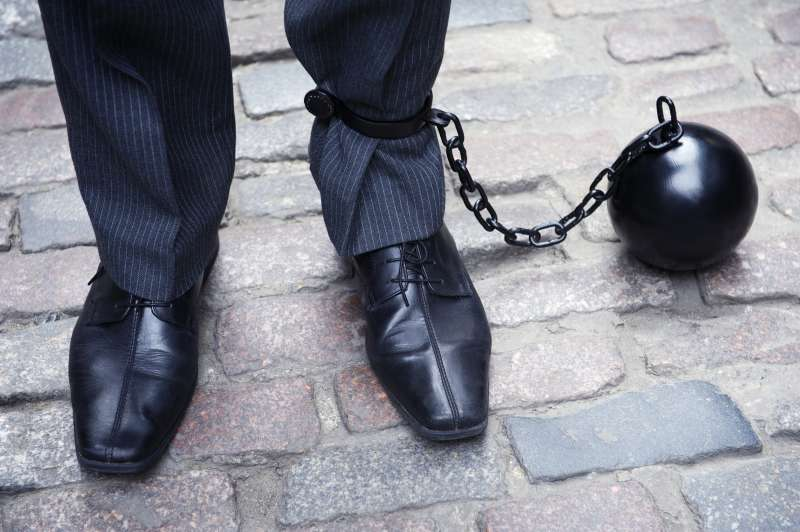 ball and chain connected to businessman's legs