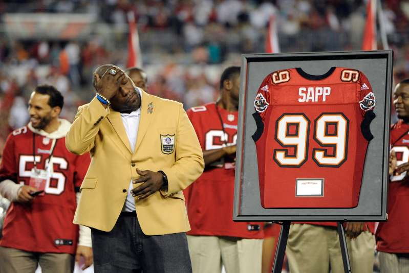 Former Tampa Bay Buccaneers defensive tackle Warren Sapp wipes his face as he is inducted into the team's Ring of Honor during half time in an NFL football game against the Miami Dolphins Monday, Nov. 11, 2013, in Tampa, Fla.