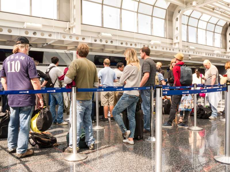 customers waiting in line at airport check-in counter