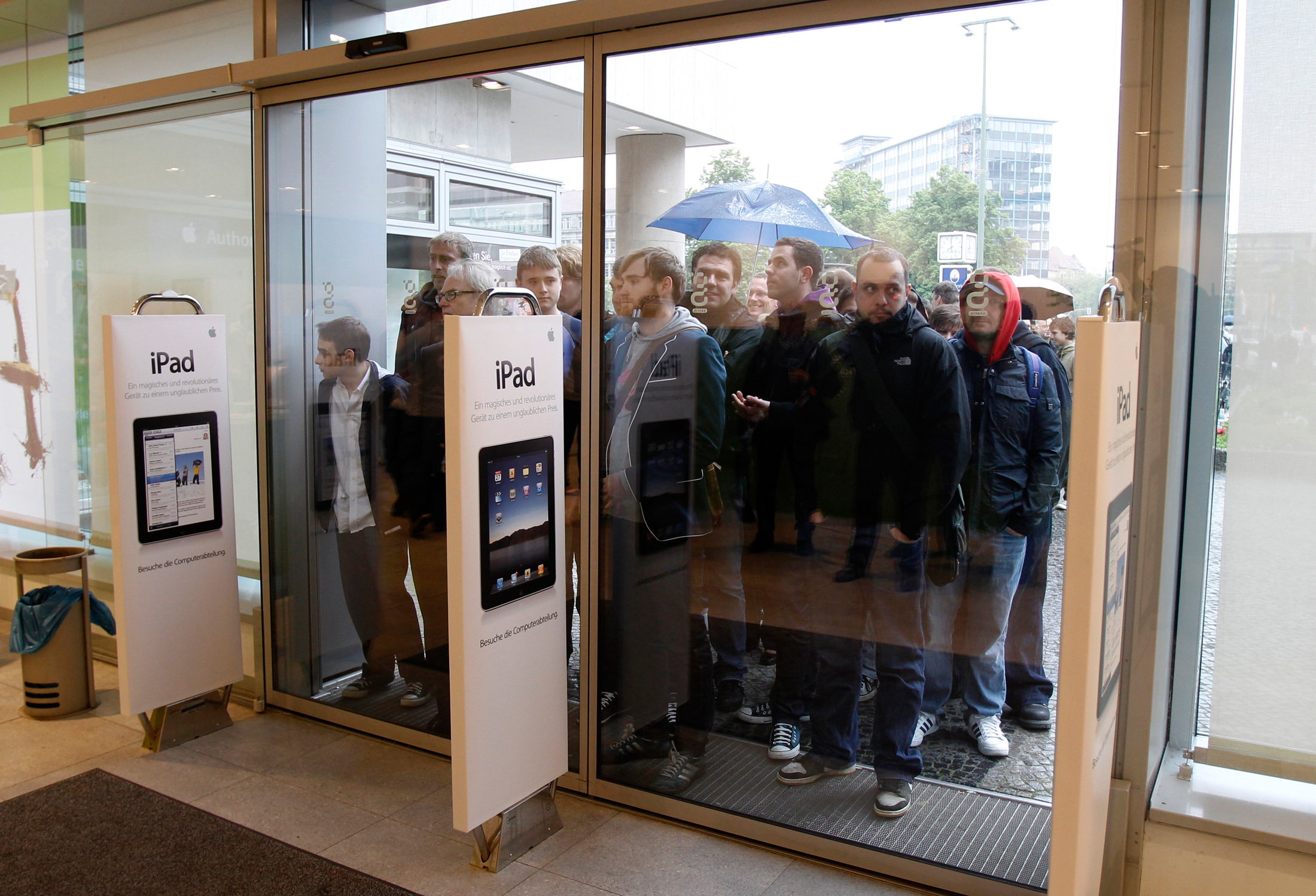 People wait in line to purchase Apple iPads during a launch event at the Apple retail store in Berlin.