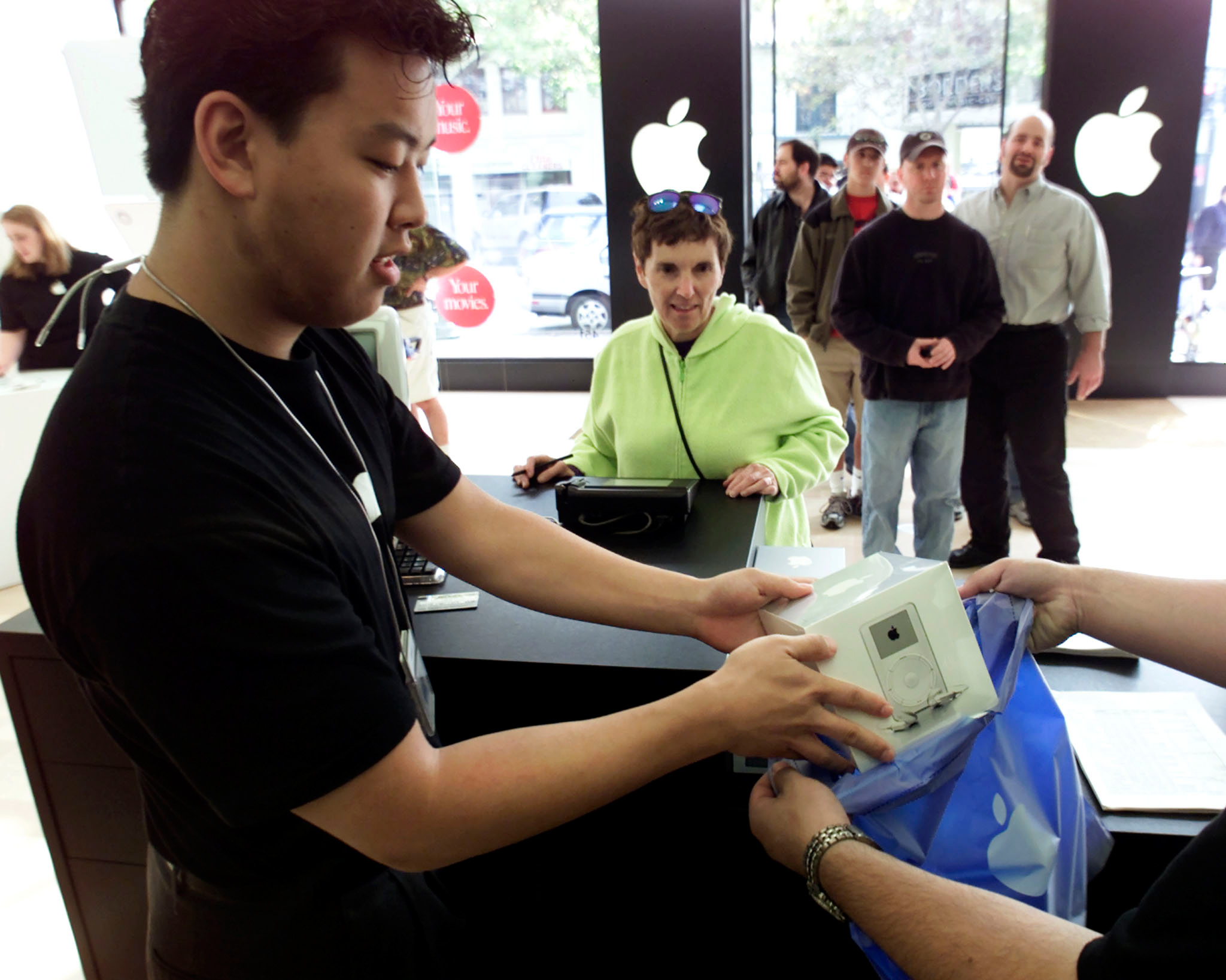 A salesperson bags a new Apple iPod MP3 player shortly after the Apple store opened in Palo Alto, California, November 10, 2001. Apple stores across the country hosted lines of eager customers wanting to be among the first to own iPod. The breakthrough MP3 player holds up to 1,000 songs and fits in your pocket.