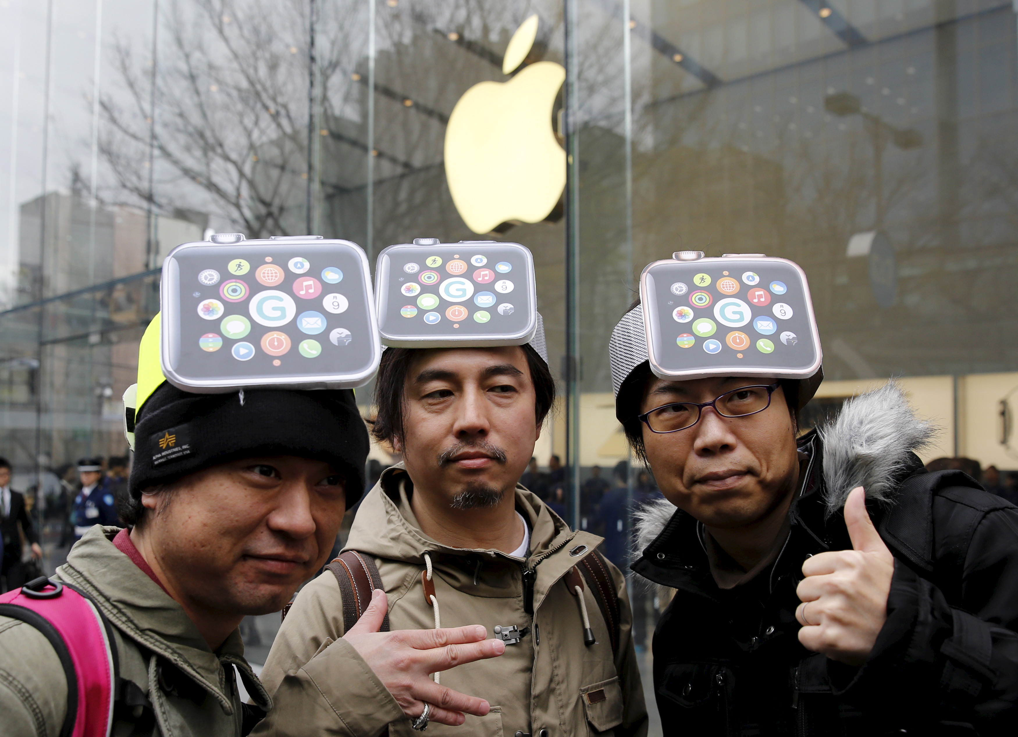 Men wearing cardboard Apple Watches on their heads pose for photos before it goes on display in front of the Apple Store in Tokyo's Omotesando shopping district.