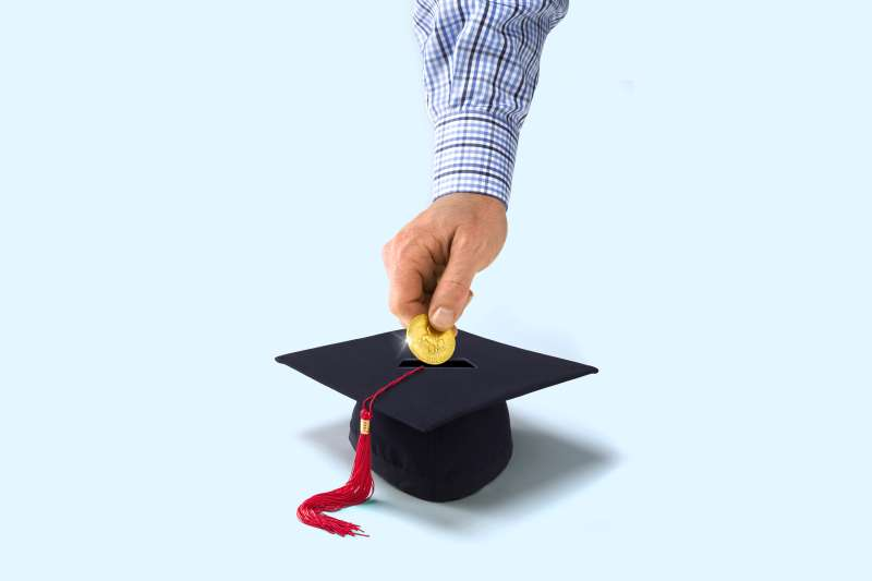 Person putting coin in mortarboard