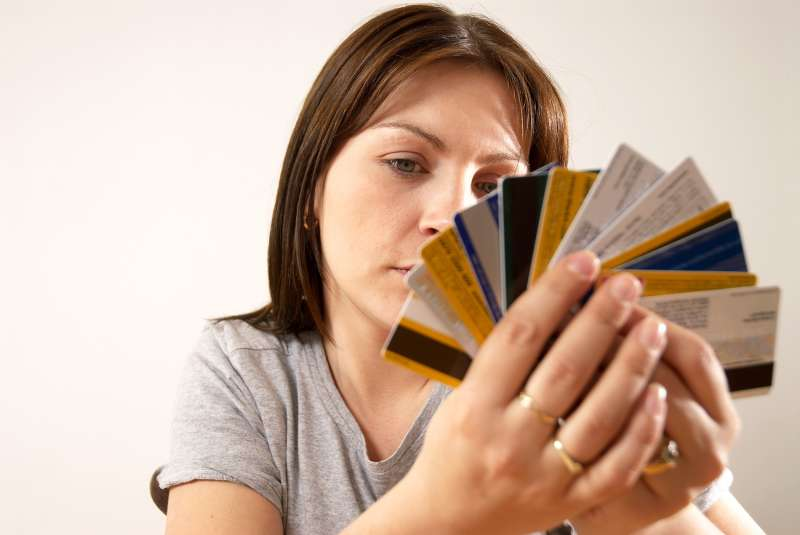 woman holding fan of credit cards