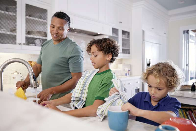 father and sons doing dishes