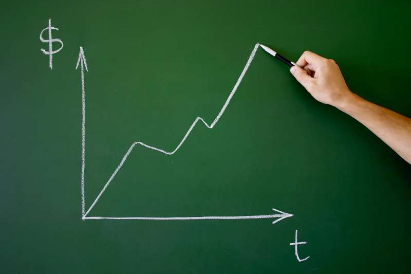 chalkboard with graph showing increase in money over time