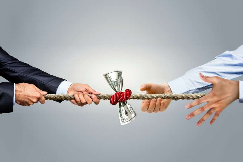 tug of war over money, one person letting go of rope