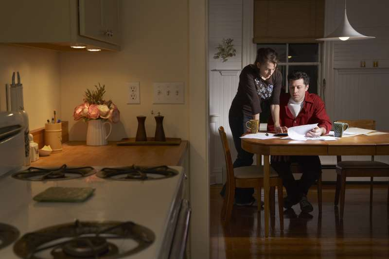 couple paying bills in kitchen