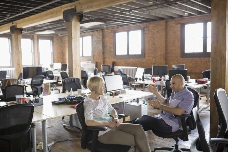 man and woman in startup company having conversation