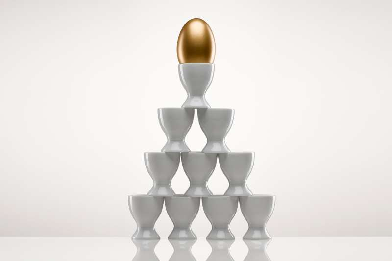 gold nest egg atop a pyramid of egg cups