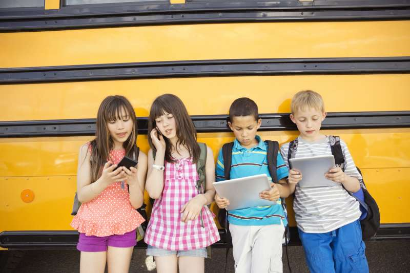 School kids using smartphones and tablets in front of school bus