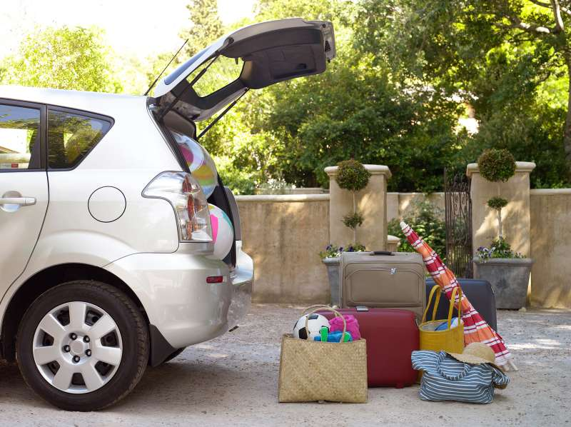 overstuffed SUV trunk with vacation luggage sitting on pavement