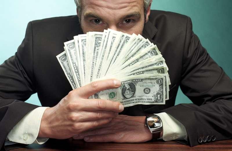 man peering over fan of cash