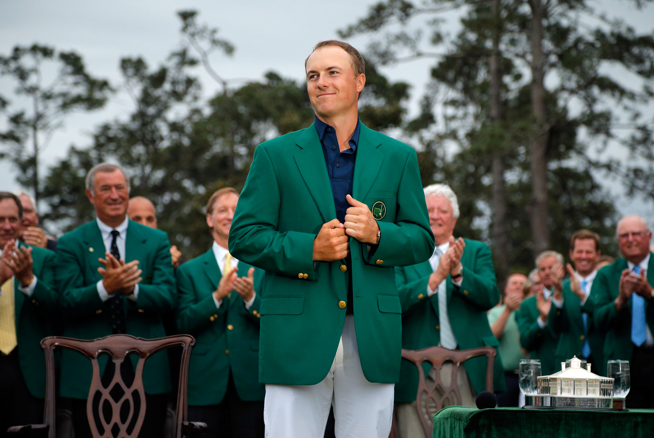 Jordan Spieth of the U.S. grins as he wears his Champion's green jacket on the putting green after winning the Masters golf tournament at the Augusta National Golf Course in Augusta, Georgia April 12, 2015.