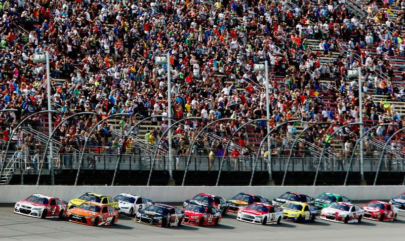 Carl Edwards, driver of the #19 ARRIS Toyota, and Kevin Harvick, driver of the #4 Budweiser/Jimmy John's Chevrolet, lead the field to a restart during the NASCAR Sprint Cup Series Quicken Loans 400 at Michigan International Speedway on June 14, 2015 in Brooklyn, Michigan.