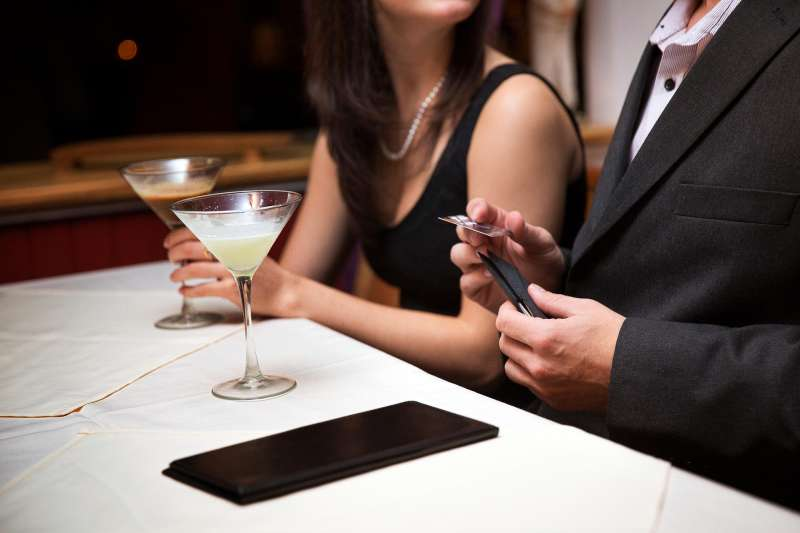 couple on first date, man paying with credit card