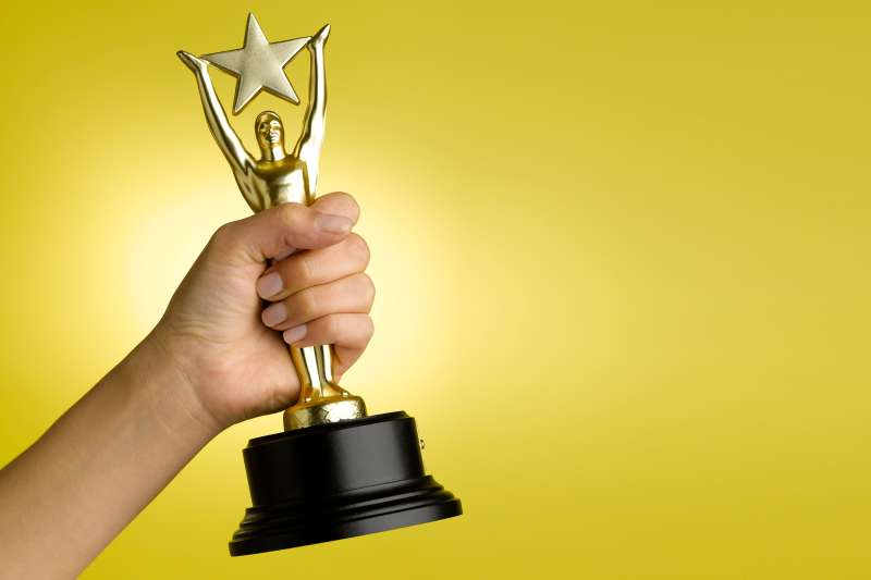 hand holding gold star trophy