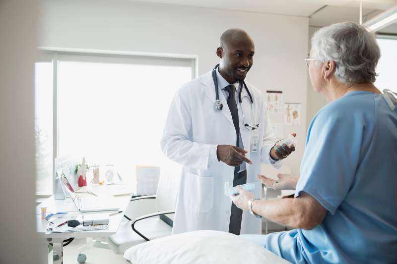 Doctor prescribing medication to senior man