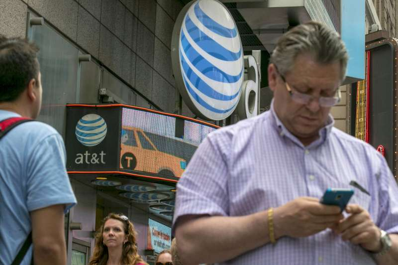 A man uses his phone outside the AT&T store in New York's Times Square, June 17, 2015.