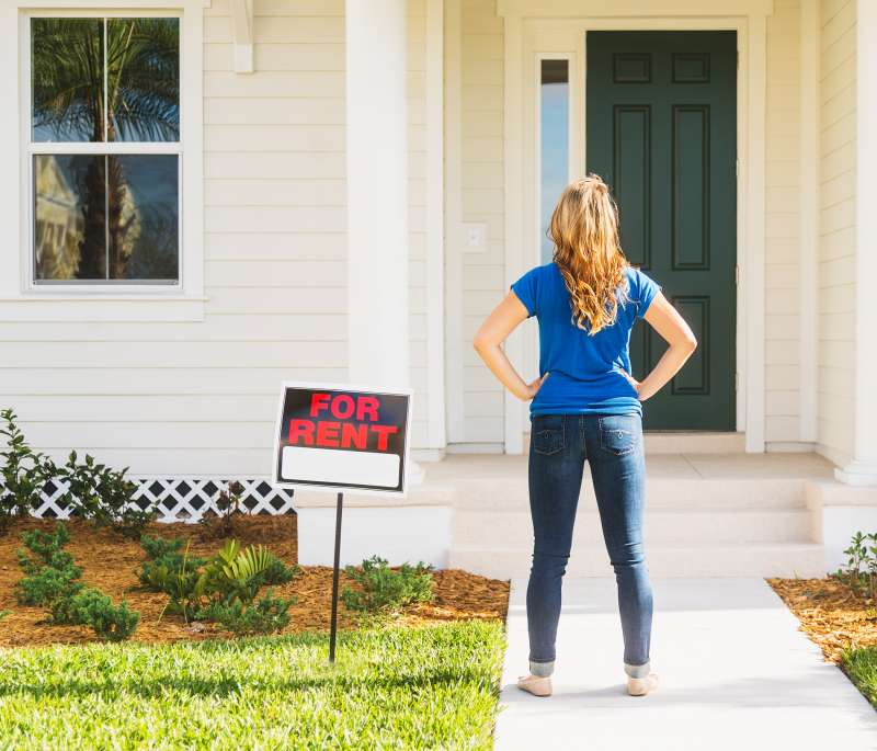 Millennial in front of house for rent