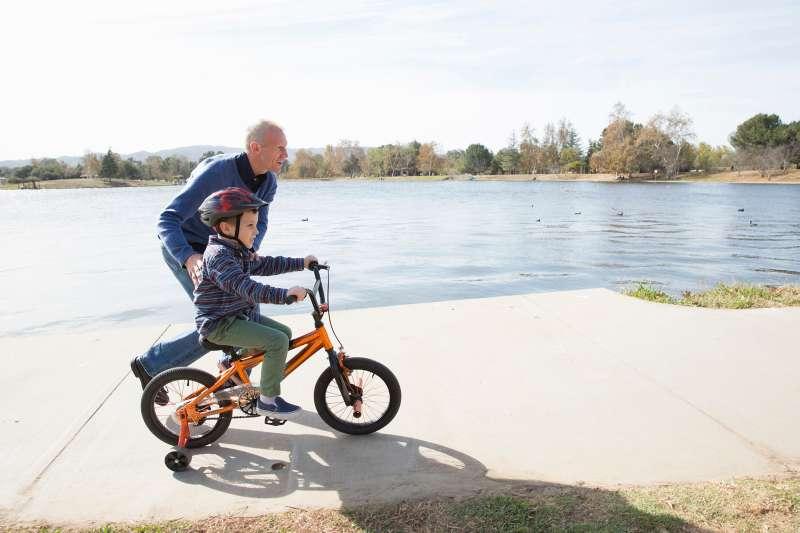 senior adult teaching child to ride bike