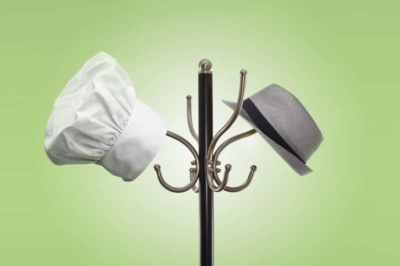 chef hat and fedora hanging on hat rack