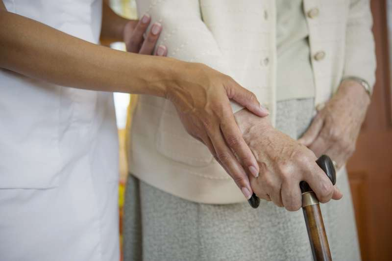 caregiver helping woman with cane