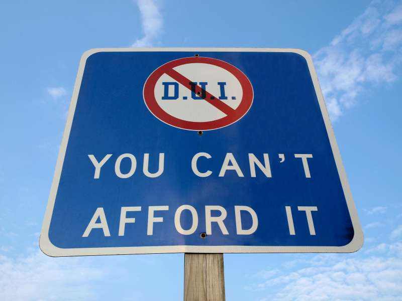 Highway sign with DUI crossed out saying  You Can't Afford It