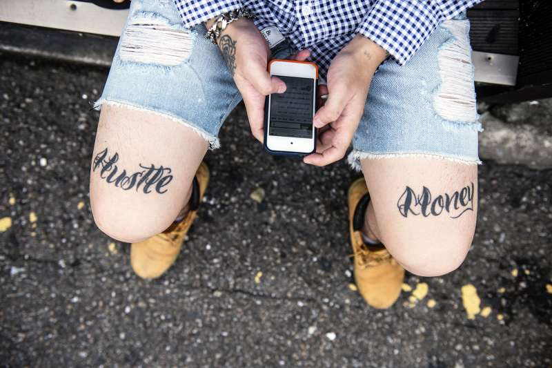 Millennial with the words  Hustle  and  Money  tattooed on each leg using his iPhone