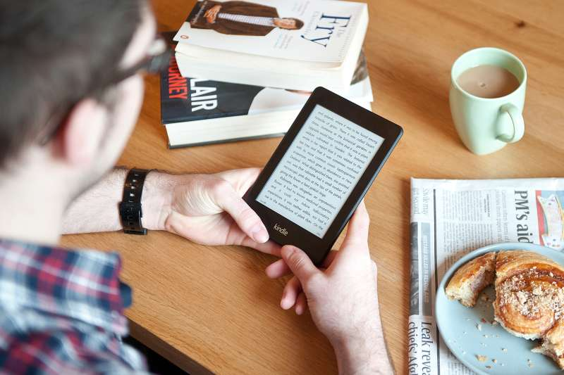 man holding amazon kindle in cafe