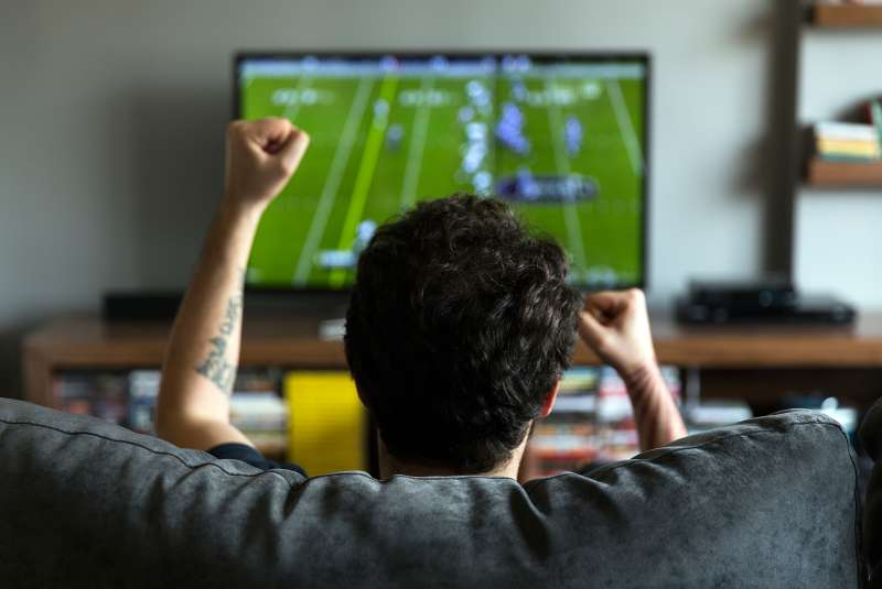 student on couch cheering at Football on TV