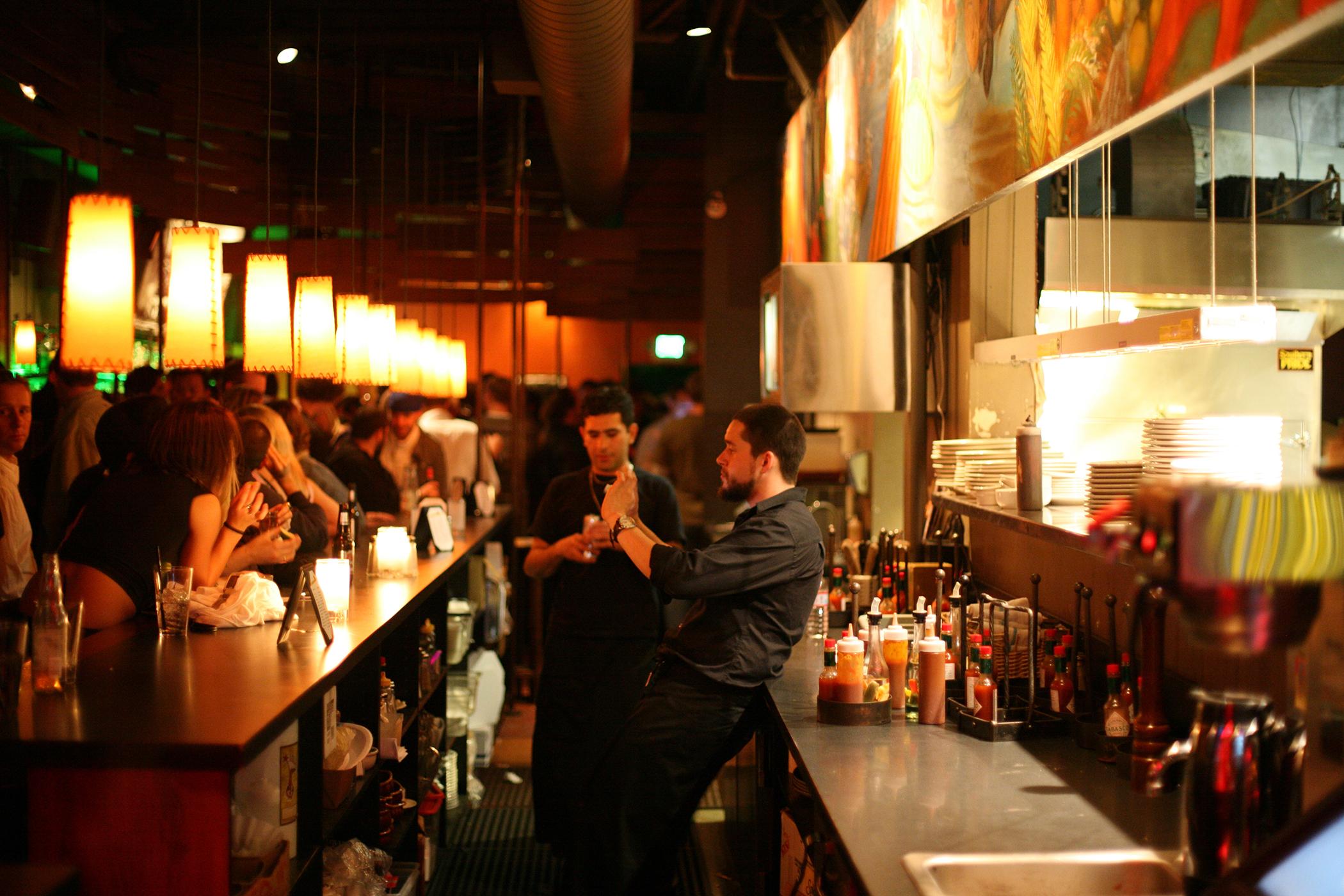 Bartender taking photograph of patrons in bar at Belltown, Seattle, Washington