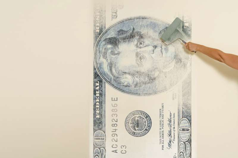 woman painting $20 bill on wall with roller