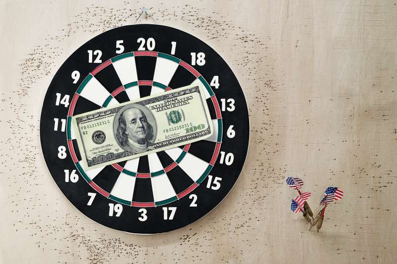 $100 bill on target and darts on wall