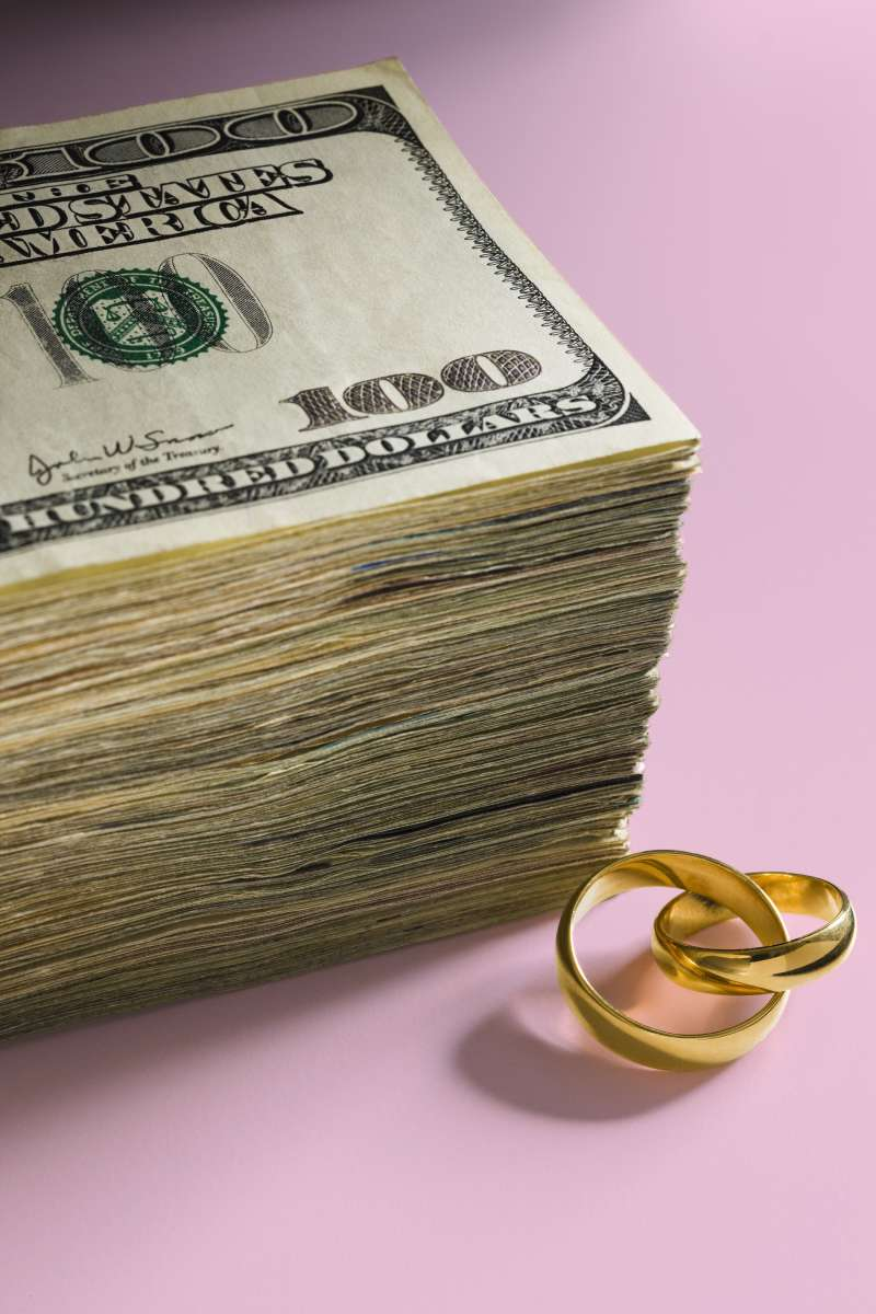 stack of cash and wedding rings