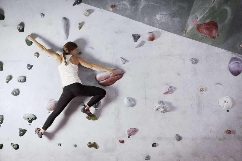 woman on rock climbing wall at gym