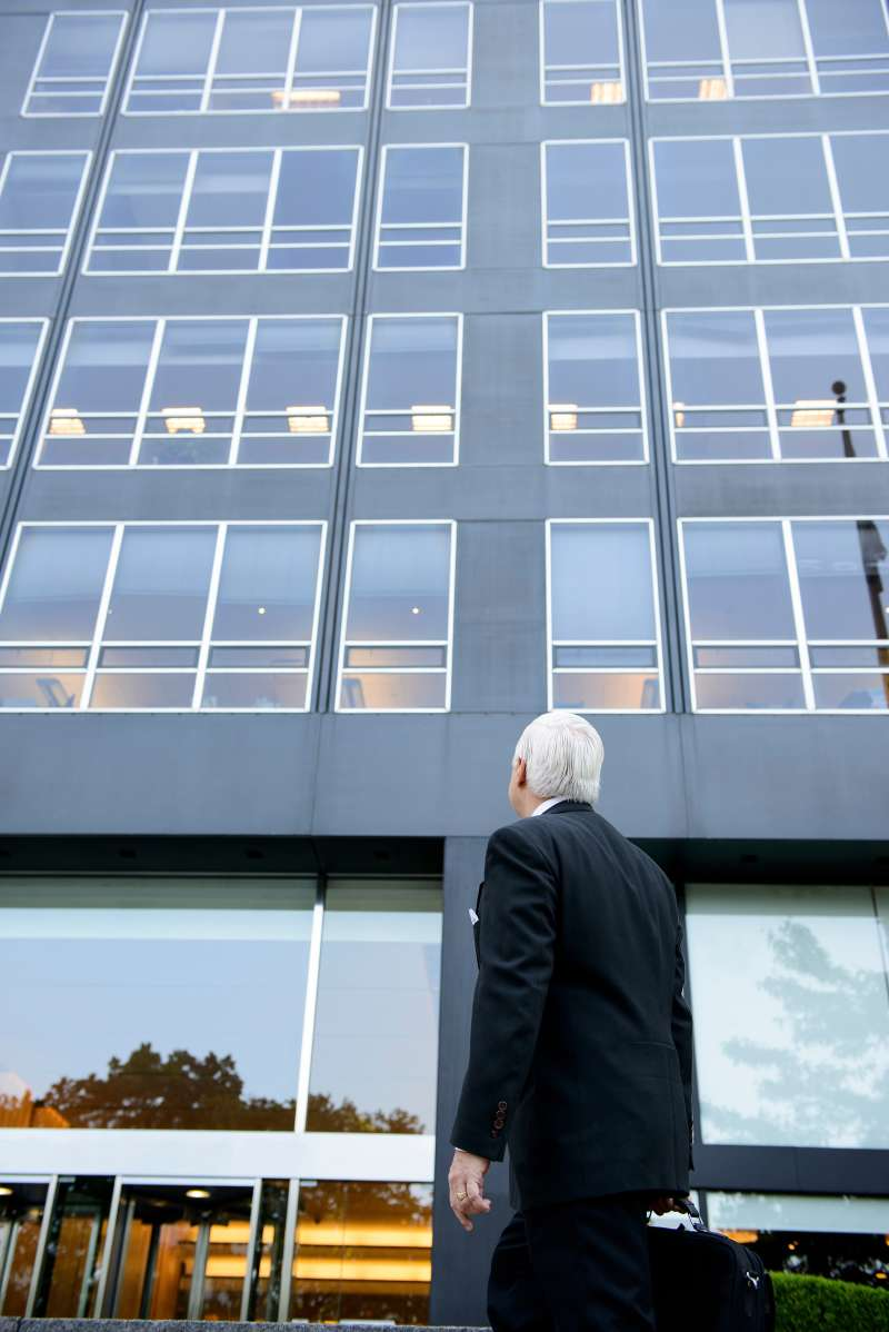 senior businessman walking into office building