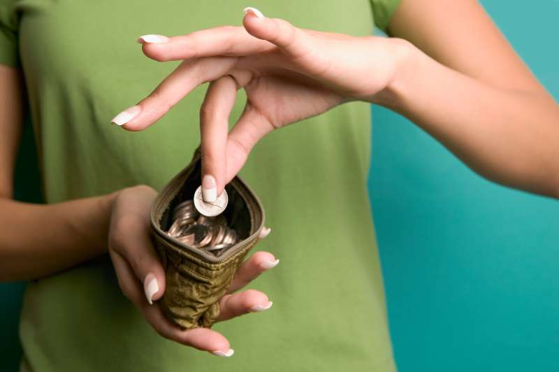 young woman putting coin in change purse