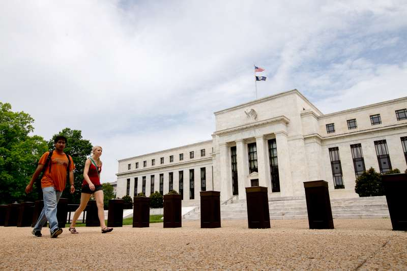 Pedestrians walk past the Marriner S. Eccles Federal Reserve Board Building, Friday, June 19, 2015, in Washington.