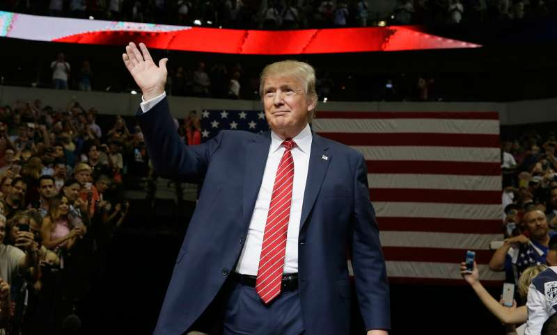 Republican presidential candidate Donald Trump waves to supporters as he takes the stage for a campaign event in Dallas, Monday, Sept. 14, 2015.