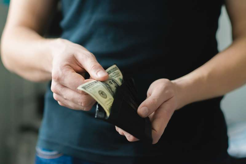 person pulling cash from wallet