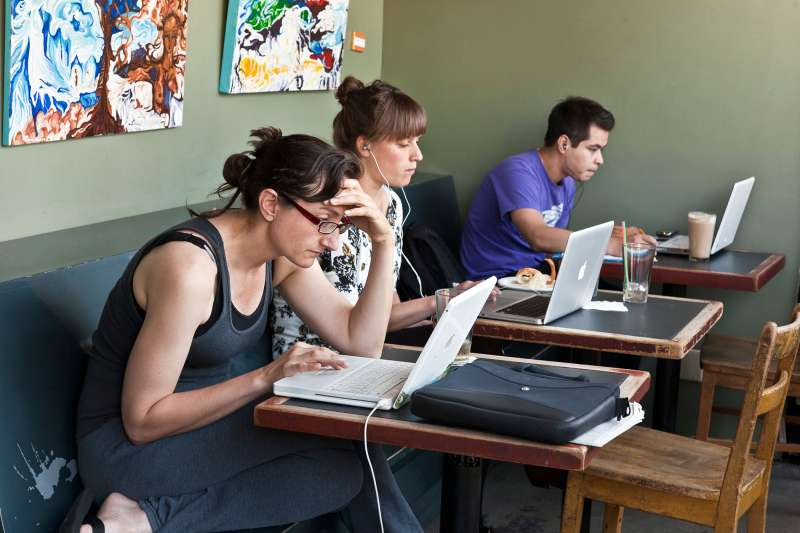 people working on computers in coffee shop