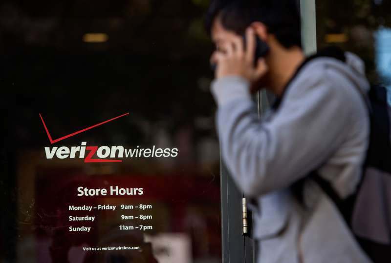 A pedestrian talks on his mobile phone while walking past a Verizon Wireless store in San Francisco, California, on April 15, 2015.