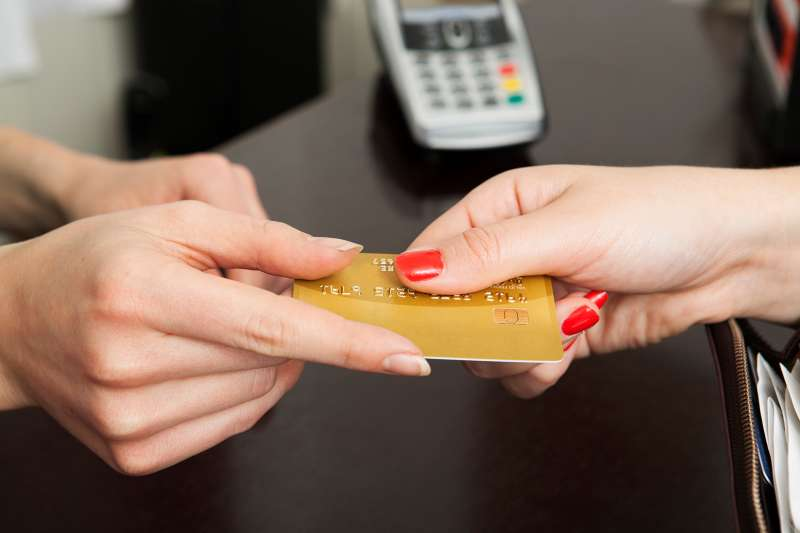 Woman handing over credit card for payment.