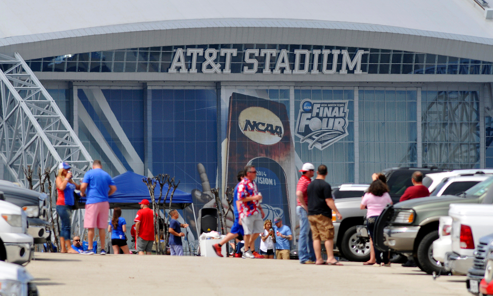 Baseball fans tailgate in the parking lots next to At&T Stadium, March 31, 2014.