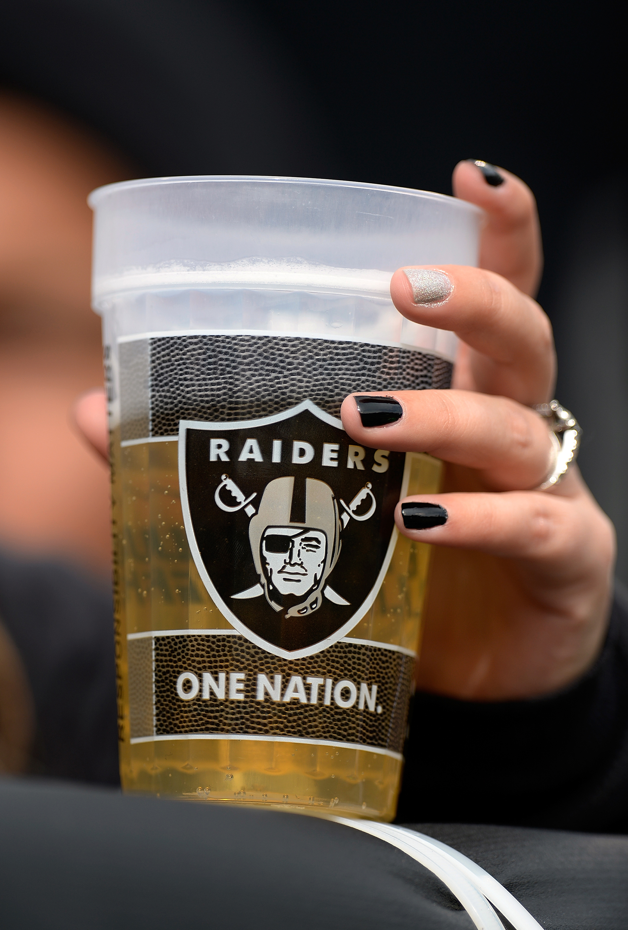 A fan holds onto her beer during an NFL Football game between the Philadelphia Eagles and the Oakland Raiders at O.co Coliseum on November 3, 2013 in Oakland, California.