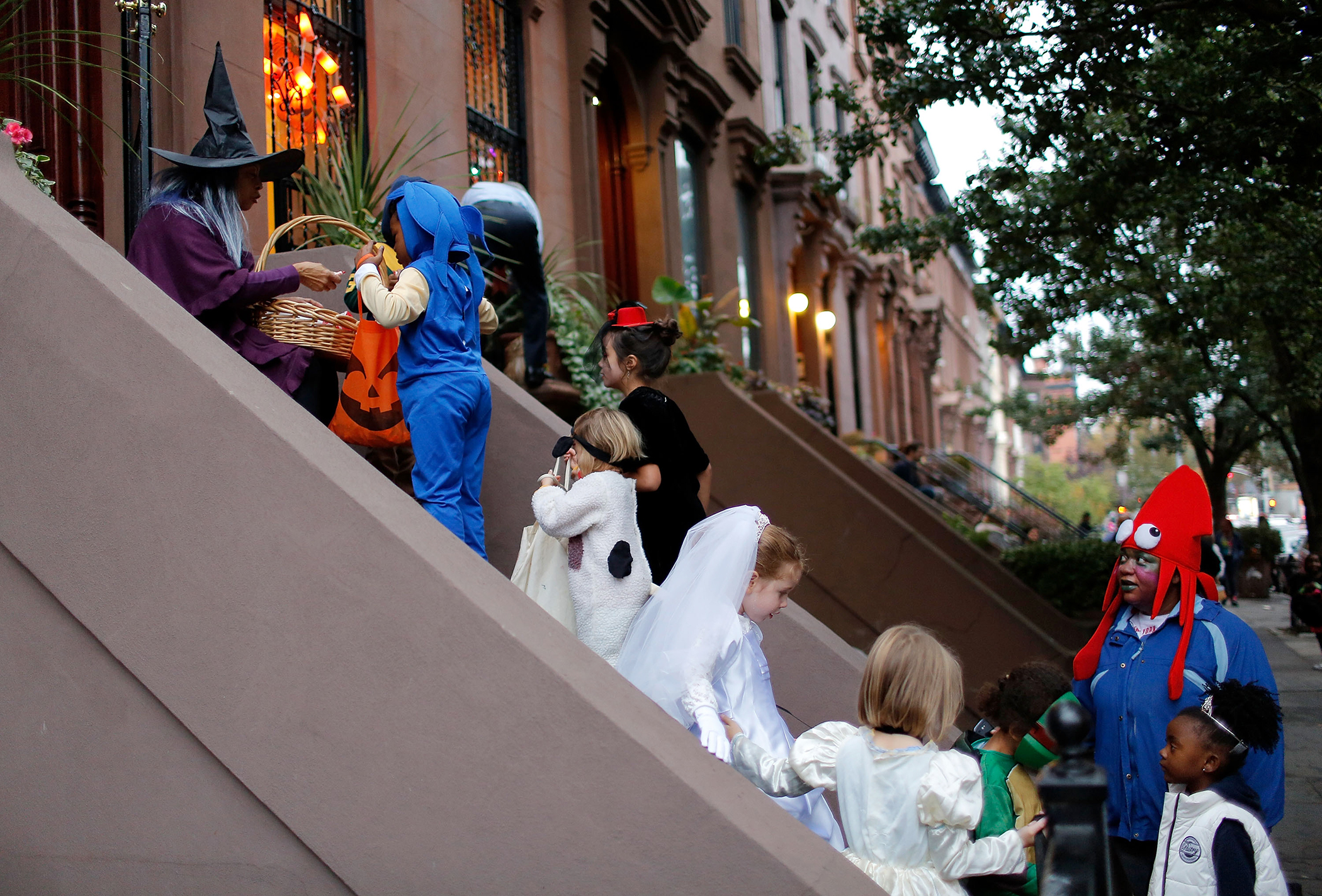 Linda Vital (L) passes out candy to halloween revelers as they stop at a private residence on Greene St. in Clinton Hill, Brooklyn to  Trick or Treat  in Clinton Hill, Brooklyn on October 31, 2013 in New York City.