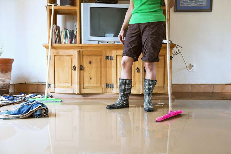 woman trying to sweep up flood